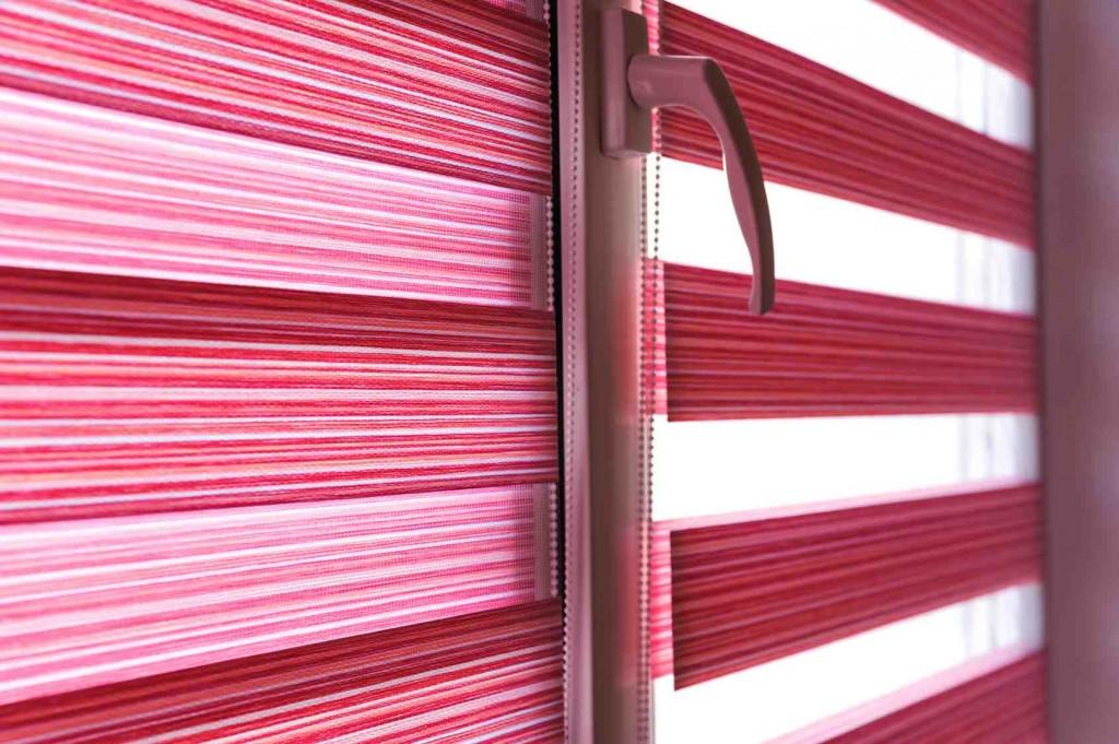 O tej porze roku, jak nigdy musimy wielokrotnie w ciągu doby manewrować przesłonami okiennymi – kiedy chcemy, by światło naturalne docierało do wnętrza i wówczas, gdy promienie słoneczne stają się zbyt dokuczliwe. Dla tych, którzy chcą, by do wnętrza docierało tyle światła słonecznego, ile akurat potrzeba w danym momencie, niezastąpione są rolety typu zebra. Łączą one w sobie wszystkie zalety zasłon, firanek i rolet. Rolety dzień i noc – optymalna funkcjonalność Rolety typu zebra należą do rolet zwijanych na wałek, który najczęściej jest schowany w aluminiowej listwie (kasecie) w górnej części okna. W wielu modelach ruch rolety odbywa się po bocznych prowadnicach. Obsługuje się je pociągając za sznurek. Możliwy jest również montaż rolet duo zatrzymywanych w dowolnej pozycji bez użycia sznurków. Pozwalają one na płynne przesuwanie tkaniny i jej ustawienie w wybranej pozycji. Taka konstrukcja przesłony sprawia, że roleta w przeciwieństwie do firanek czy zasłon zawsze przylega do okna i nie łopocze przy przeciągach czy dużym wietrze. Część materiałową rolet dzień i noc tworzy tkanina z wzorem poziomych pasów na przemian przezroczystych lub półprzezroczystych oraz zaciemniających. Dzięki takiej tkaninie można uzyskać bardzo zróżnicowany stopień zaciemnienia i dopływu światła słonecznego do wnętrza. Przesuwanie względem siebie nałożonych podwójnie tkanin daje bowiem niezliczone możliwości ustawienia. Fragmenty nieprzejrzyste skutecznie chronią naszą prywatność, natomiast przez pasy transparentne możemy mieć doskonały widok na otoczenie.  Rolety duo – duet pełen urody Rolety zebra to nie tylko rozwiązanie bardzo praktyczne, ale są również efektowną ozdobą wnętrza. Modny horyzontalny układ pasów tkaniny tworzy efektowny wzór doskonale wpisujący się w estetykę nowoczesnych wnętrz. Naprzemienność transparentnych i nieprzezroczystych pasów dodaje wnętrzom lekkości i energii. Mimo że jednokolorowe, to jednak nie są monotonne, kombinacja przezroczystych i nieprzejrzystych pasów